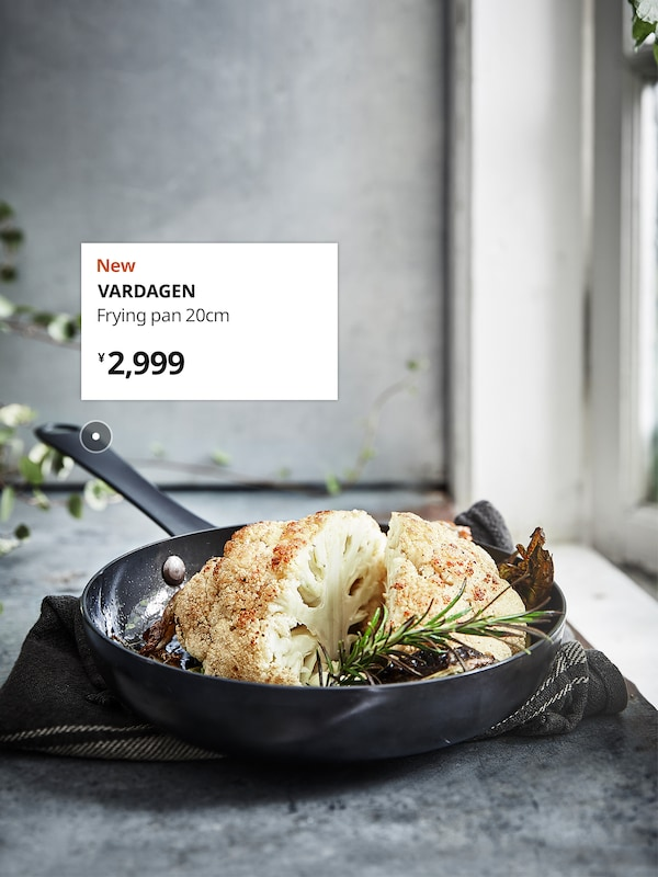A black VARDAGEN frying pan placed on a grey marble countertop with a frying pan and kitchen accessories at the back.