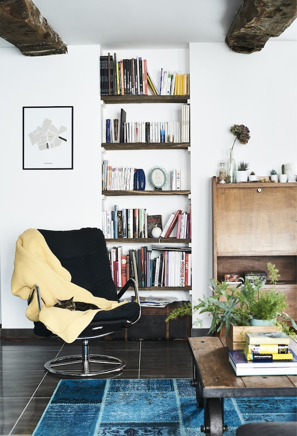 A black vintage IKEA swivel chair with yellow throw tossed onto it in an white walled, open airy living space.