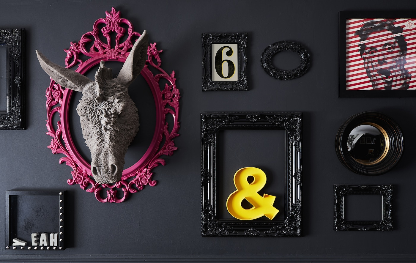 A black wall decorated with different frames and objects, with pops of pink and yellow.