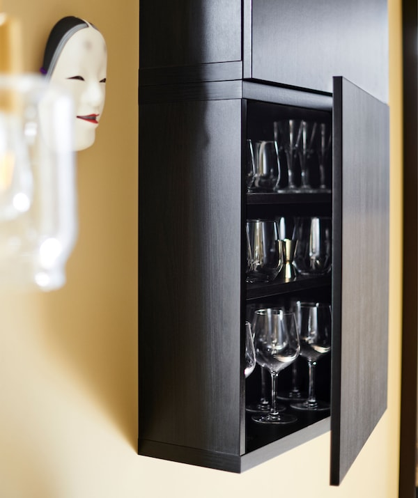 A black wall-mounted cupboard with its door opened to reveal glassware inside.