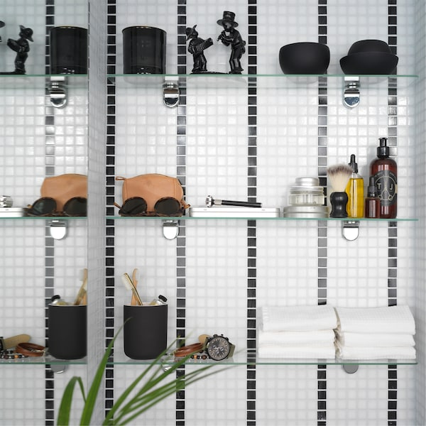 A black/white striped bathroom tile wall where 3 glass shelves are mounted and store towels, decorative items, and more.
