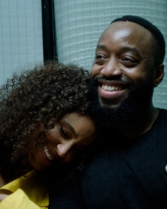 A Black woman with curly hair rests her head on the shoulder of a Black man with facial hair.