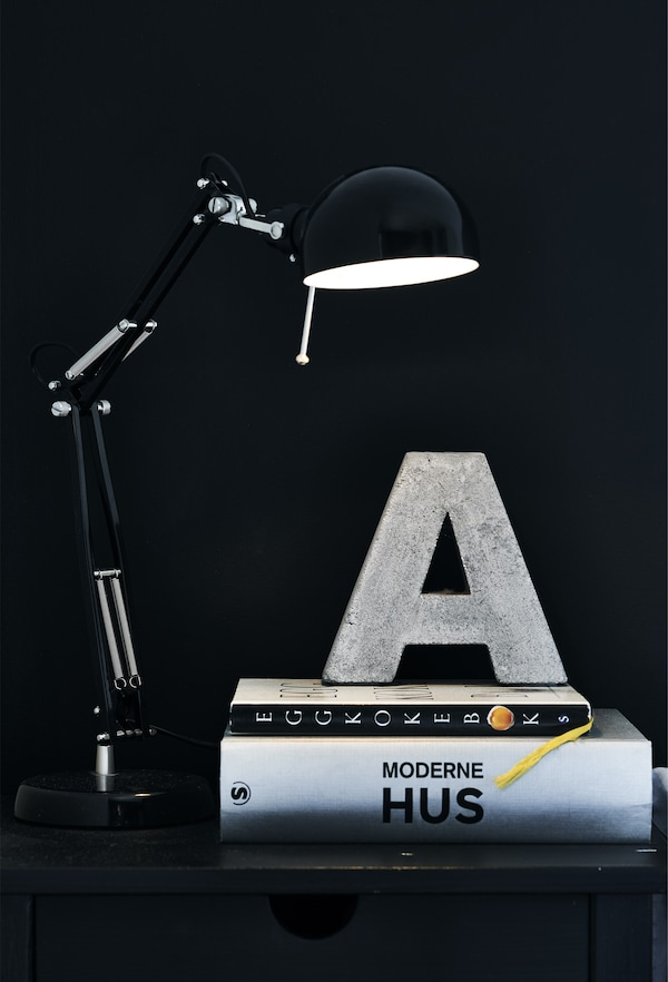 A black work lamp lights up the capital letter a made of concrete placed on a stack of books.