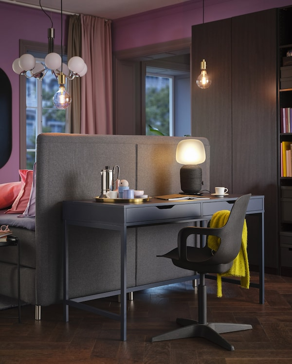 A blue ALEX desk, a lit table lamp and a black swivel chair with a yellow throw are standing at the back of a bed headboard.