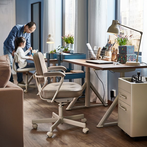 A blue and beige home office, with a father and daughter in the background.