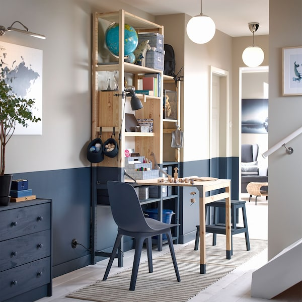 A blue and beige themed hallway containing an IKEA IVAR storage unit with a foldable table furnished as a hobby station.