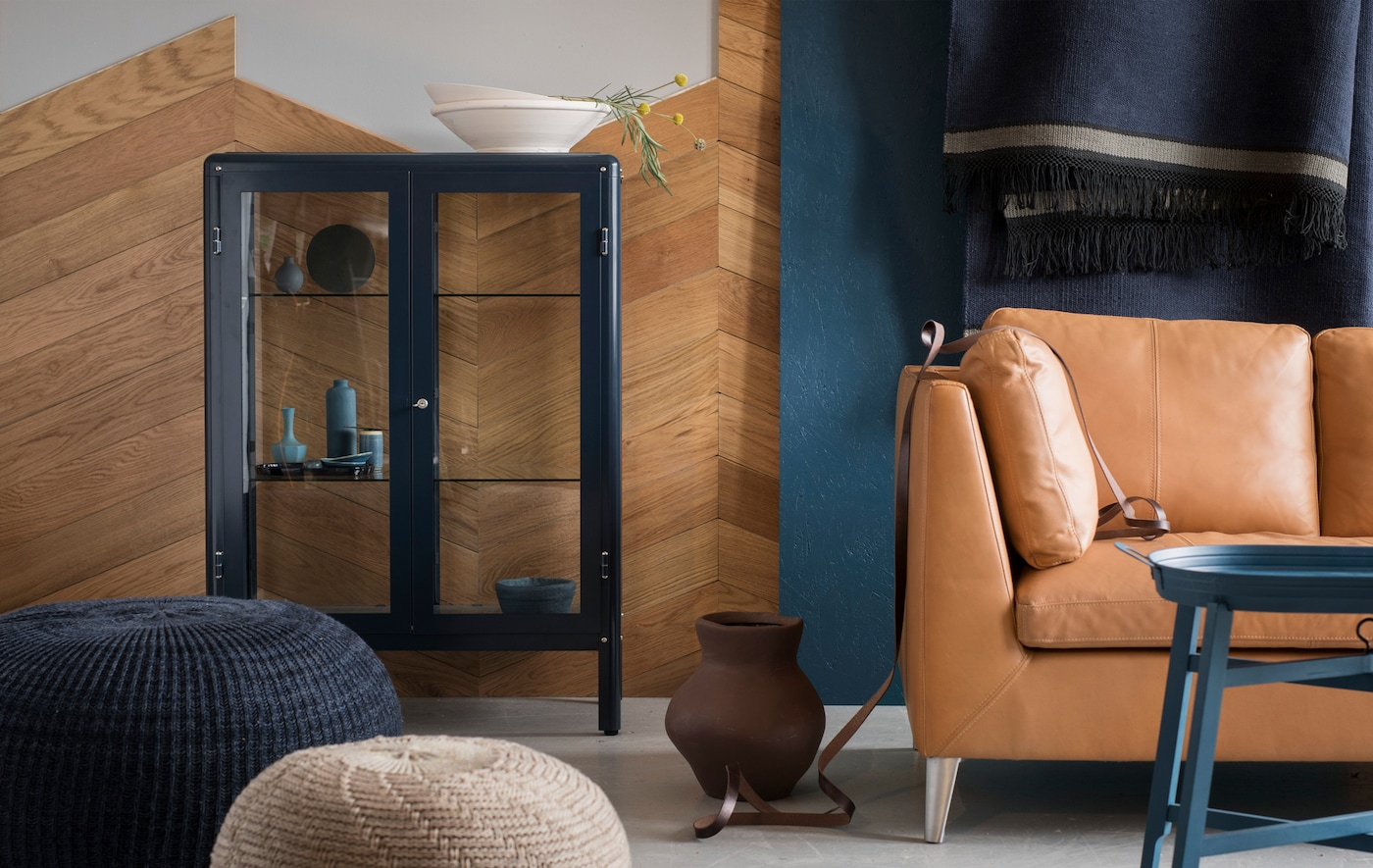 A blue and brown living area with a sofa, footstools and an IKEA FABRIKÖR glass-door cabinet in blue.