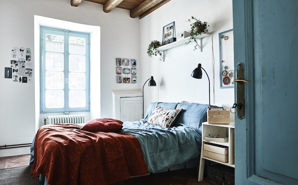 A blue and white bedroom, with a red bed cover.