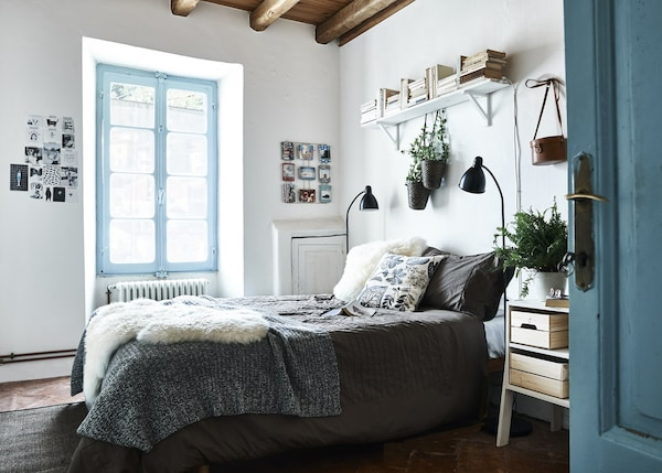 A blue and white bedroom with cosy textiles.