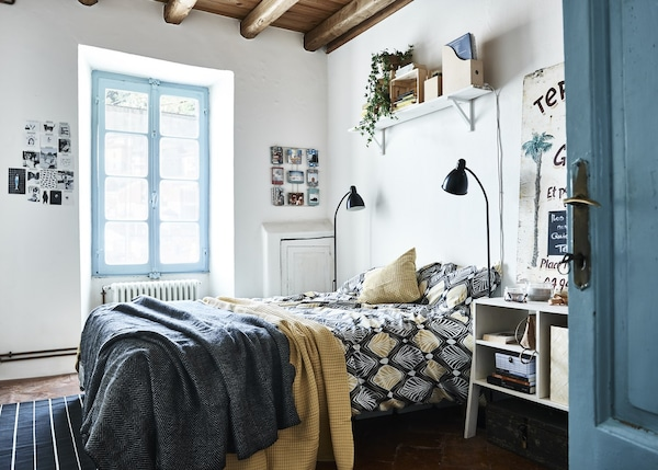A blue and white bedroom with yellow accents.