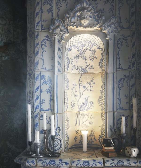 A blue and white Delftware pottery-style fireplace surround with candles and an illuminated torch on top.