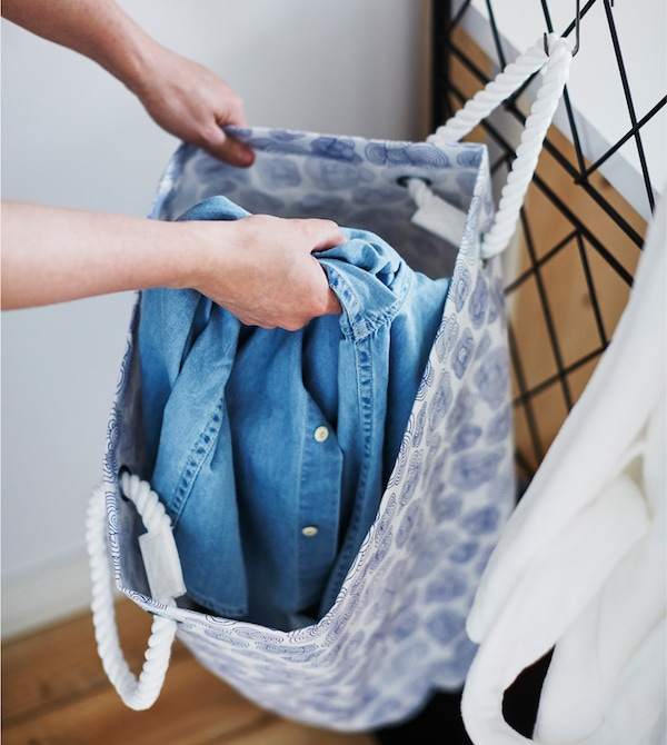 A blue and white laundry bag hangs from a black trellis.