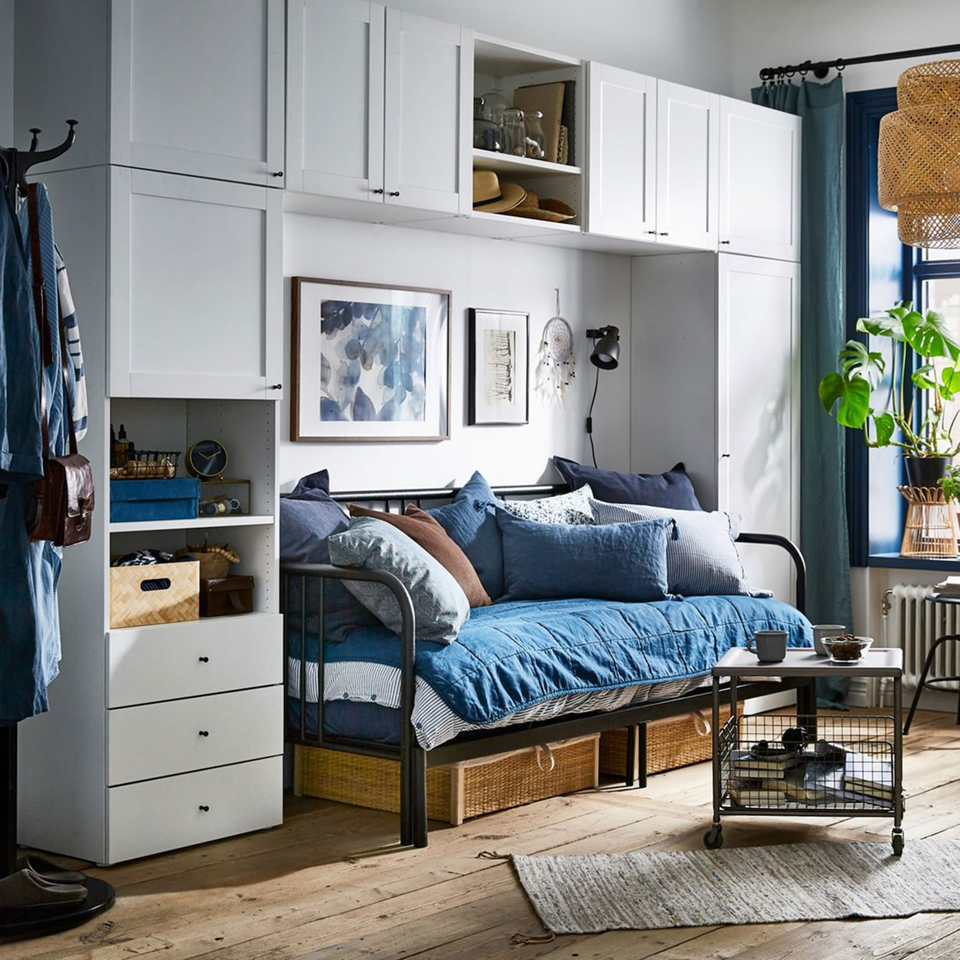 A blue and white studio apartment with the white PLATSA wardrobe arranged around a sleeping/living room zone.
