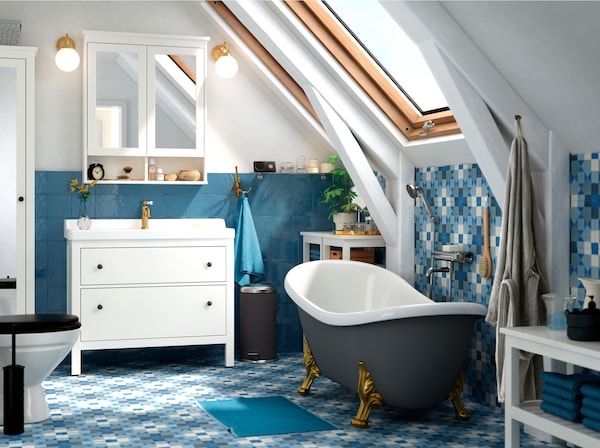 A blue bathroom with grey bath tub, a sloping ceiling and an IKEA HEMNES/RÄTTVIKEN wash-stand and mirrored wall unit.