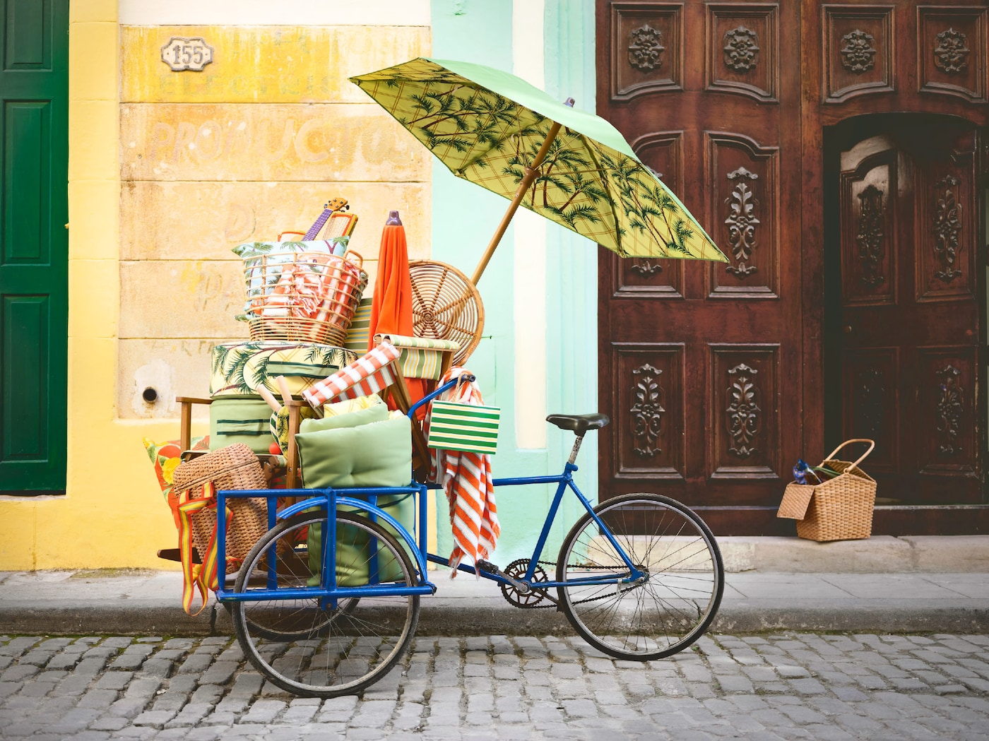 A blue bicycle standing on a cobblestone road, stacked with beach style furniture from the IKEA SOLBLEKT Collection.