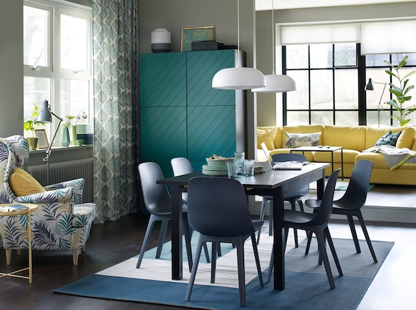 A blue, brown and green dining room with six ODGER blue dining chairs and a yellow sofa in the background.