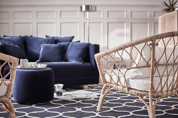 A blue couch and a chair, with a grey rug