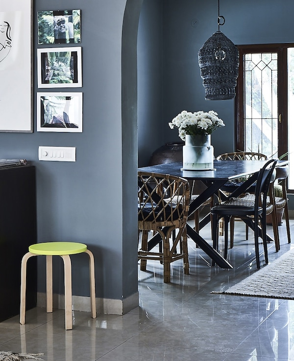 A blue dining area with new and vintage furniture.