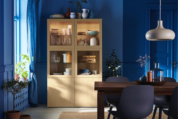 A blue dining room with a natural wood storage cabinet with plates, cups, and bowls inside