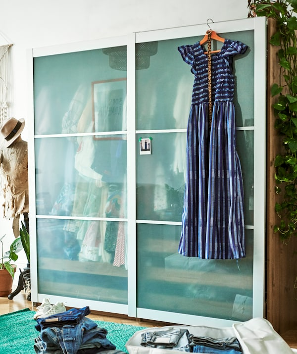 A blue dress hangs on the front of a wardrobe with sliding doors with a tailor's dummy beside it and jeans piled in front.