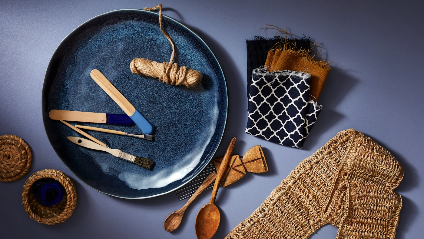 A blue ERTAPPAD dish holding a roll of string and paint brushes, besides fabric samples and wooden spoons.