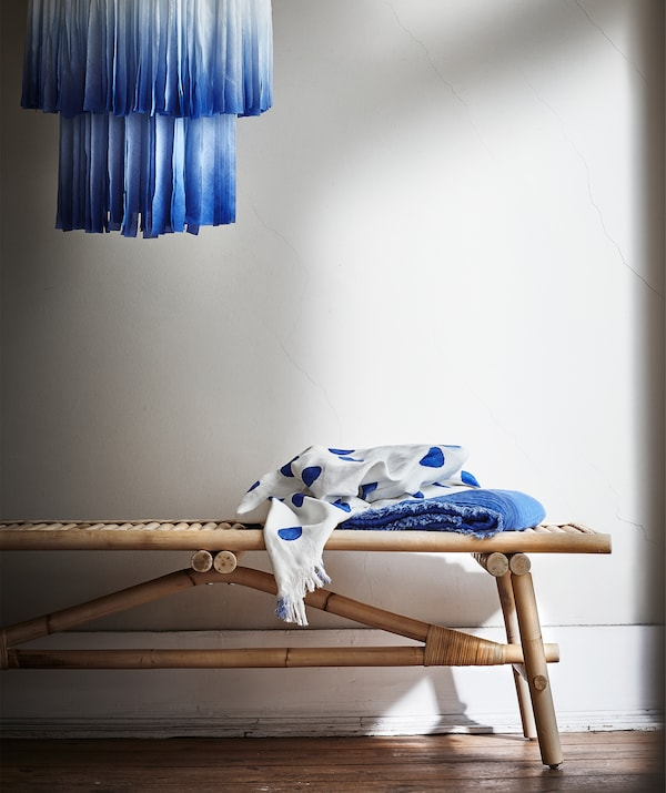 A blue fabric TÄNKVÄRD lampshade hanging above a rattan bench, with folded fabric at one end of the bench.