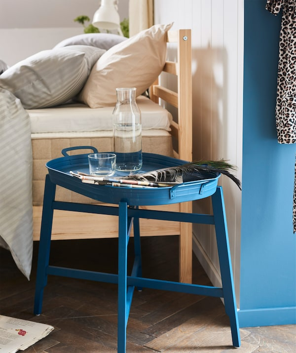 A blue FRIDAFORS tray table as a bedside table