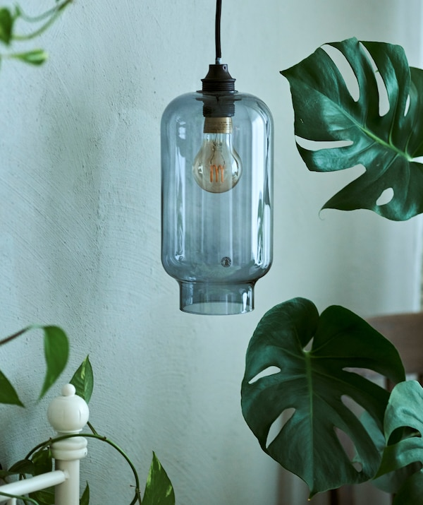 A blue glass pendant lampshade hanging beside a white bedframe, next to a MONSTERA plant.