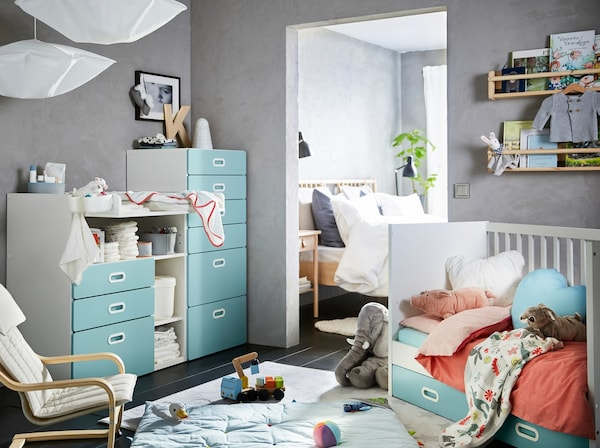 A blue, grey, red and white nursery with a white and light blue STUVA/FRITIDS changing table, chest of 6 drawers and cot.