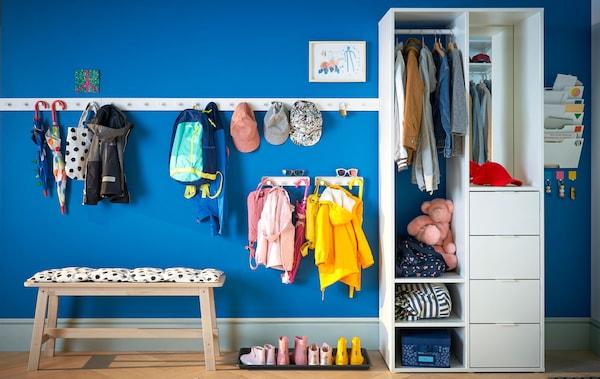 A blue hallway with coat racks, a bench and wardrobe storage.