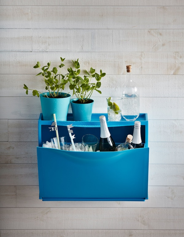 A blue IKEA TRONES shoe cabinet becomes a drink station. It's filled with ice, glasses, and bottles. Plants sit on top.