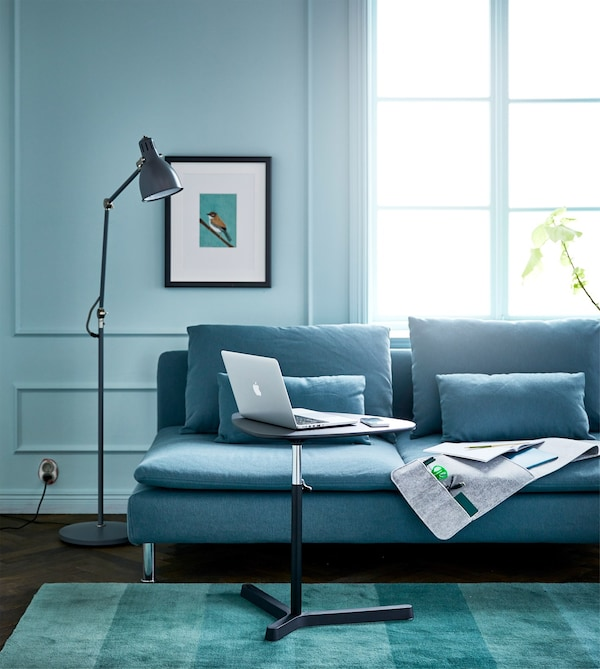 A blue living room with a sofa and adjustable laptop stand for a workspace at home.