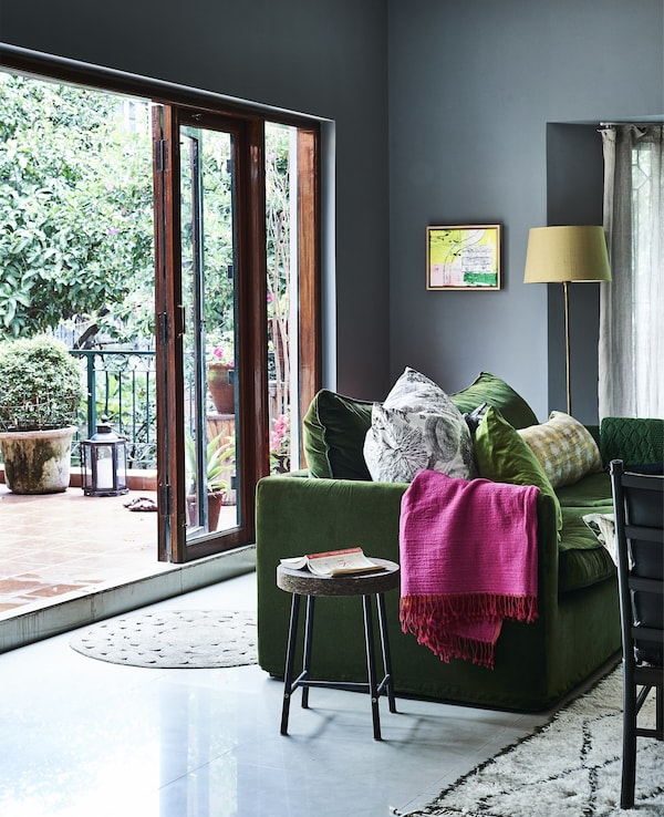 A blue living room with brightly coloured textiles.