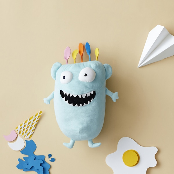 A blue monster soft toy in a fun paper cut-out scene.