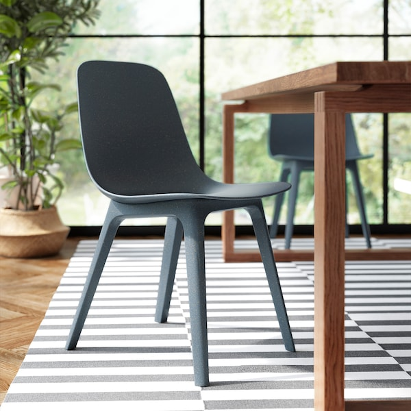 A blue ODGER chair is pulled out beside a dark wood table. There is a striped rug under the chair and table and a large plant in the background.