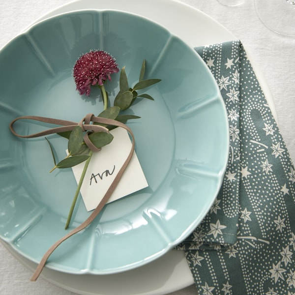 A blue plate with a pink flower placed on top.