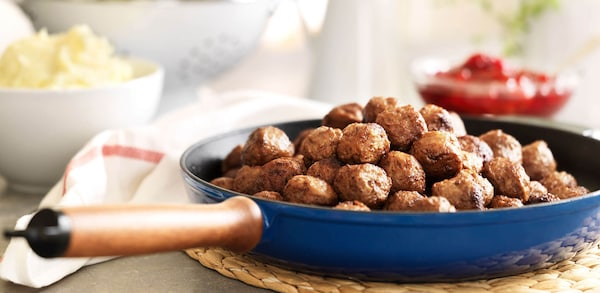 A blue saucepan with a pile of meatballs, sitting on a cooling pad on a table with side dishes.