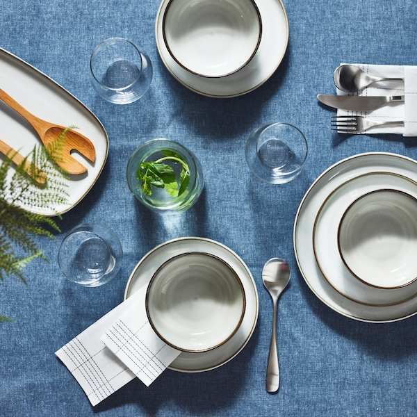A blue SEVÄRD tablecloth covered with GLADELIG bowls on different-sized plates, with glasses, cutlery and napkins around them.