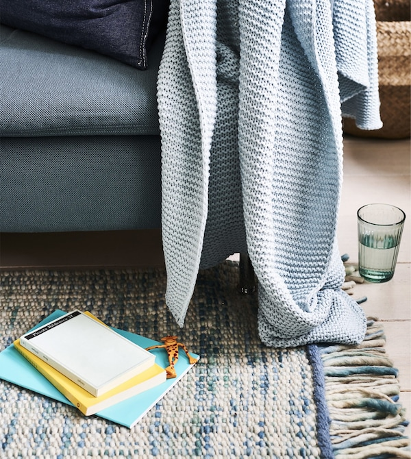 A blue sofa with blue blanket on a blue rug.