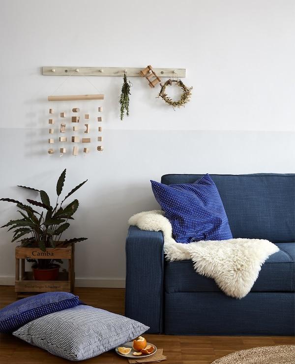 A blue sofa with sheepskin rug and blue cushions.