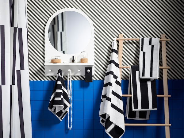 A blue striped bathroom, a SALTRÖD mirror with a shelf and hooks and a VILTO towel stand with a striped towel.