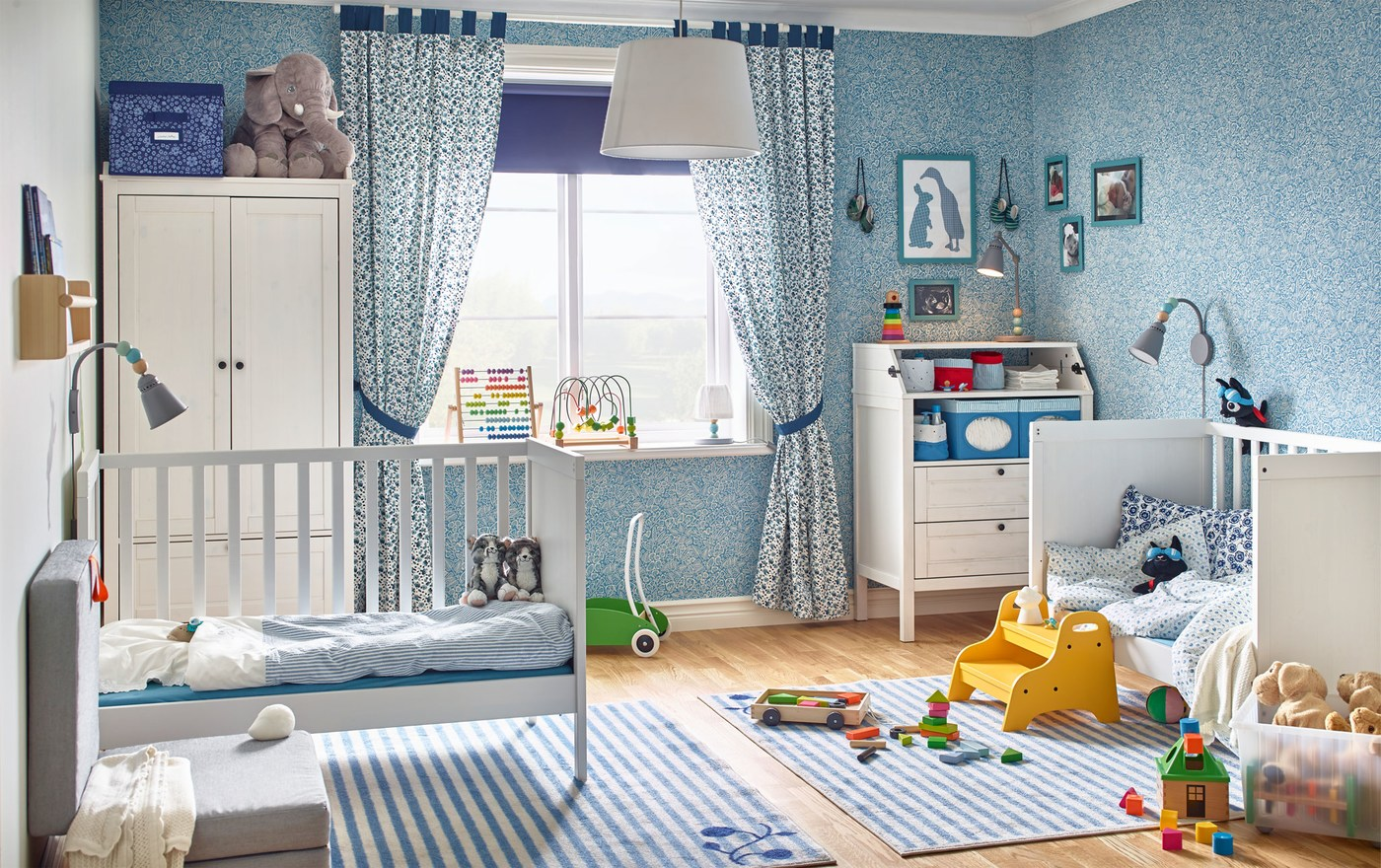 A blue themed baby bedroom with two IKEA SUNDVIK white cots, an IKEA SUNDVIK changing table and a white wardrobe.