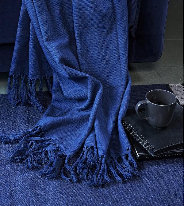 A blue throw draped on a blue rug.