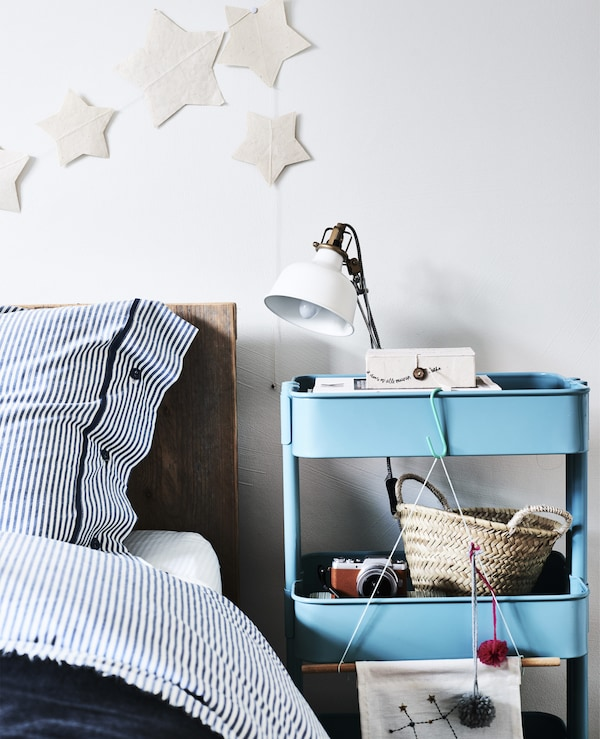 A blue trolley used as a bedside table with lamp.