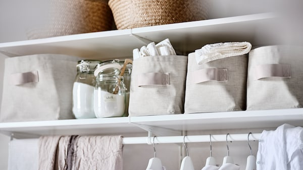 A BOAXEL system of white shelves, with glass jars containing washing powder and PURRPINGLA storage boxes.