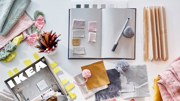 A bookmarked IKEA catalogue, an open notebook, a cup of coloured pencils and fabric samples in various colours.