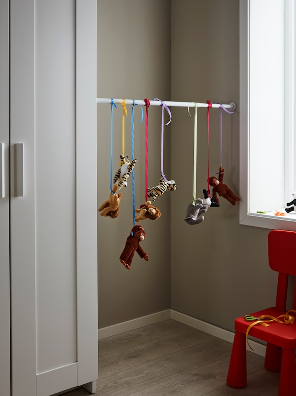 A BOTAREN rod between a wardrobe and an opposing wall with a row of DJUNGELSKOG animals hanging in coloured ribbons from it.