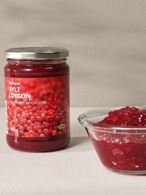 A bottle of ligonberry jam sits next to a glass bowl of lingonberry jam.