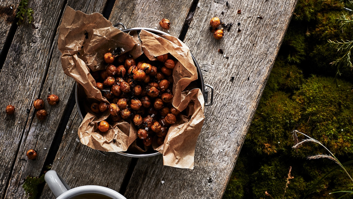A bowl lined with paper on a rustic wooden table, filled with toasted chai and chilli chickpeas. A cup is nearby.
