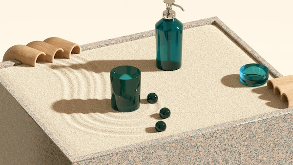 A box with sand and green bathroom containers including a soap dispense and a cup, with three marble like balls.